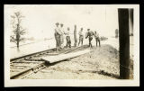 Mississippi Flood, men roping off section of train tracks; 1927.
