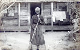 Postcard of African American woman with broom in front of house