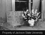"Photograph of flowers and sign ""If I die two shall take my place"" at door of Alexander..."