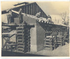 Men in PW uniforms building the structural supports/roof trusses for the roof a a lean-to; circa...