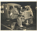 Men in PW uniforms working on a U.S. Army ambulance; circa 1940-1945