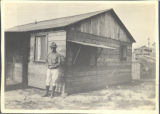 Man Standing Outside a Wooden House